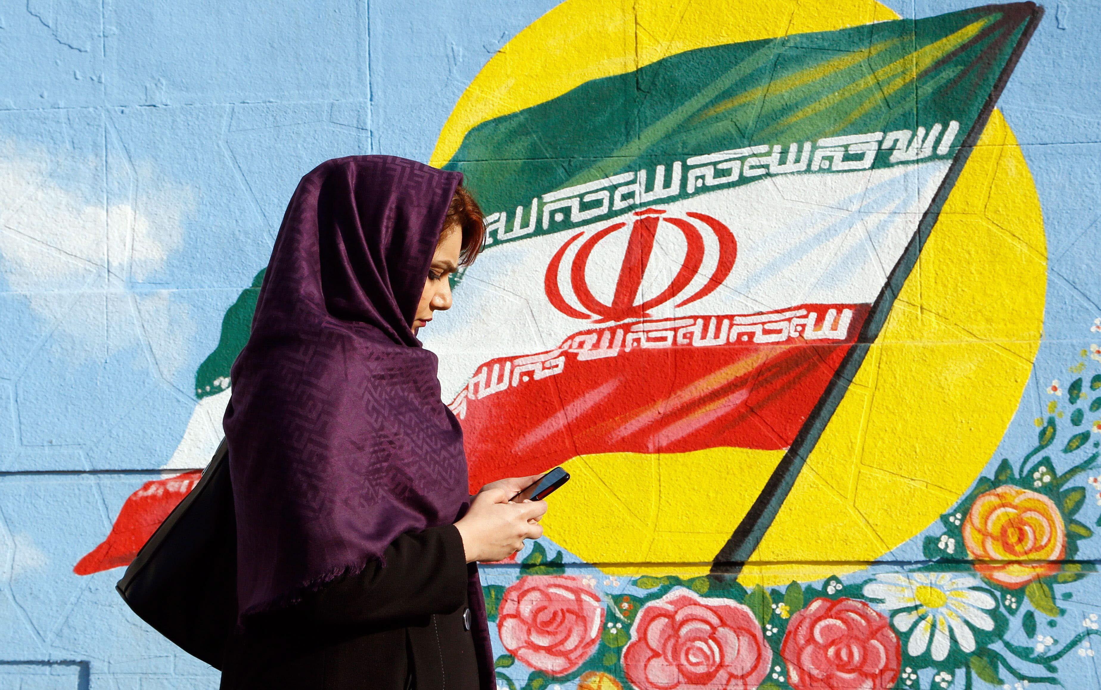 Una mujer iraní consulta su móvil en una calle de Teherán. EFE